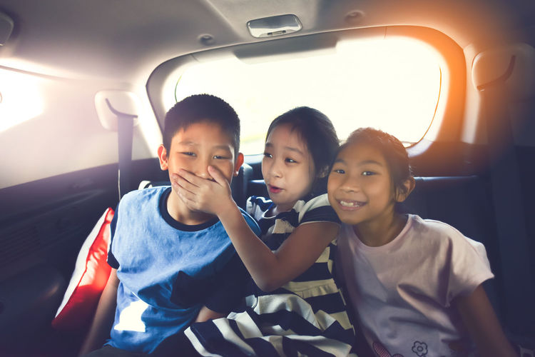 Happy Siblings Sitting In Car