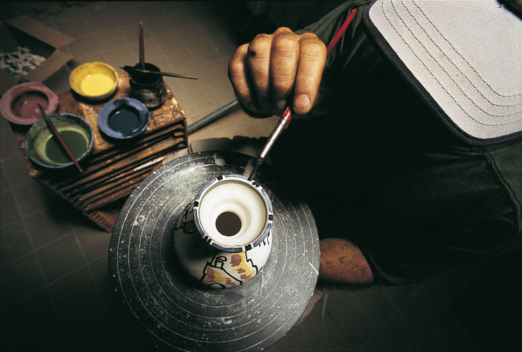 High angle view of man painting over earthenware