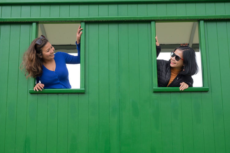 Smiling friends looking through window of shed