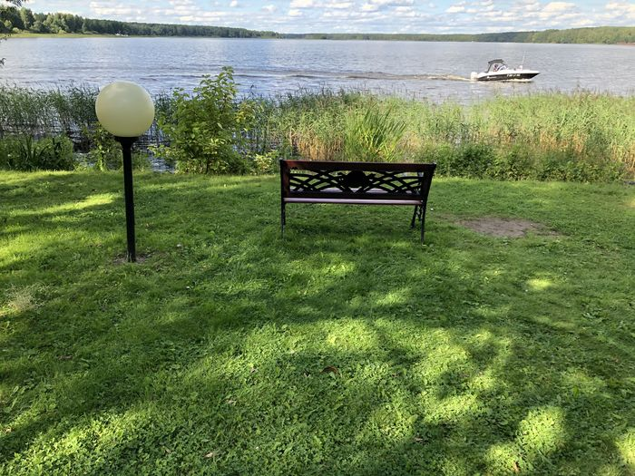 Bench on grass by sea