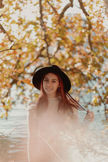 Portrait of young woman standing against tree