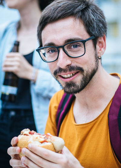 Close-up portrait of man eating burger