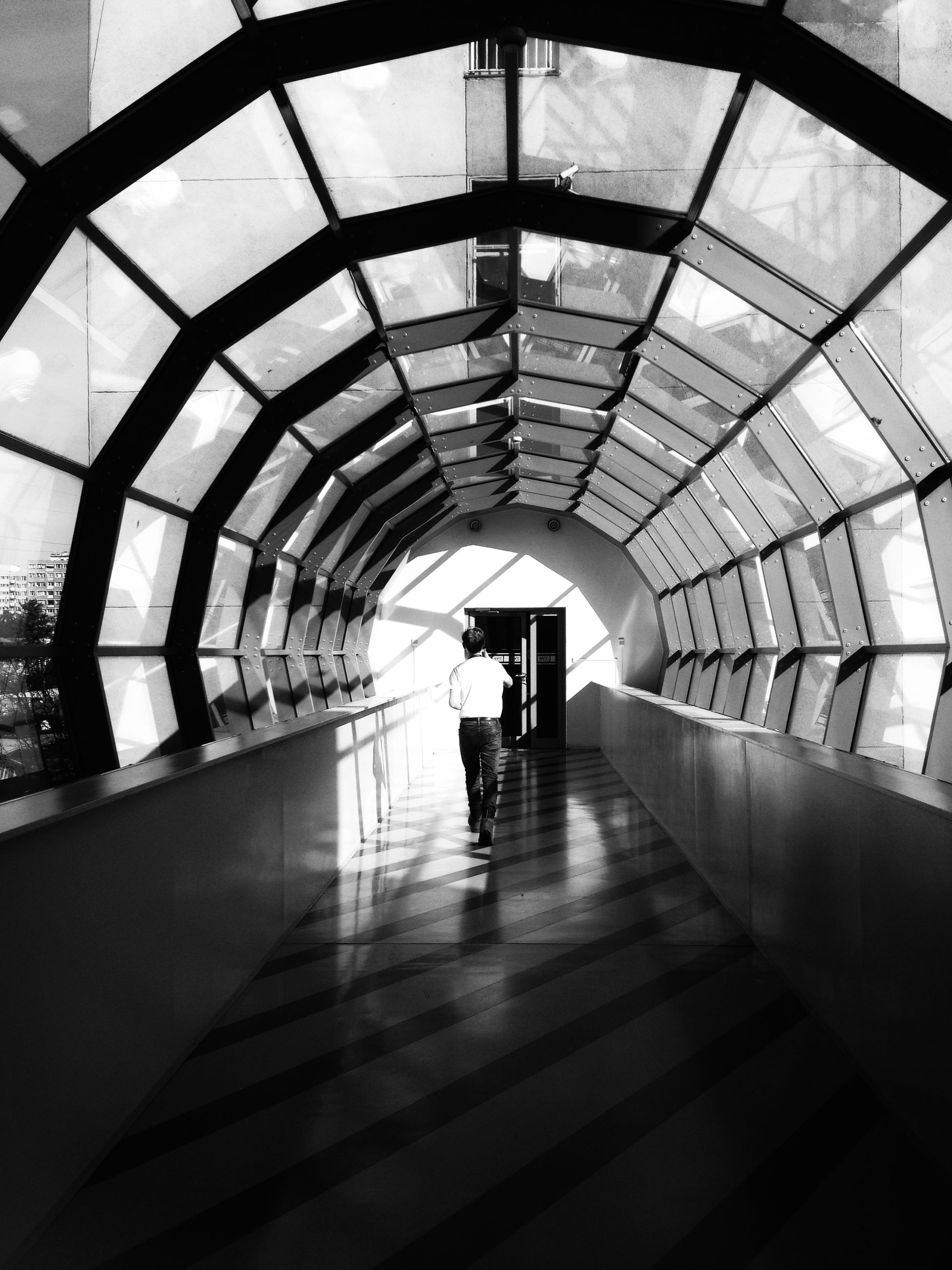 real people, architecture, indoors, built structure, walking, lifestyles, arch, the way forward, men, silhouette, rear view, leisure activity, modern, transportation, one person, women, full length, day, people