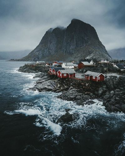 Houses by sea against mountains and sky