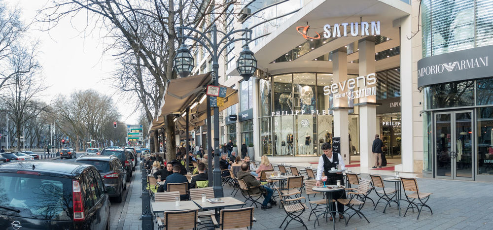 DUESSELDORF, GERMANY - MARCH 12, 2017: Unidentified shoppers stroll along the Königsallee and pass a scenic cafe with unidentified individuals Architecture Building Exterior Built Structure Chair City Citylife Day Düsseldorf Group Of People Königsallee Large Group Of People Life Style Luxury Men Outdoors P People Real People Rhein Shopping Sitting Sky Tree Visitors Women