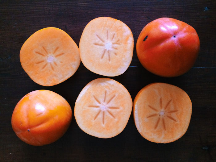 Directly above shot of halved persimmons on table