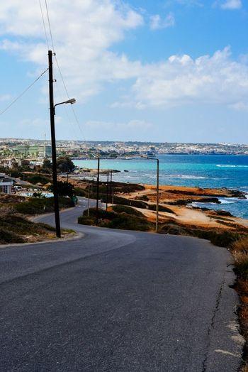 Empty road against calm blue sea