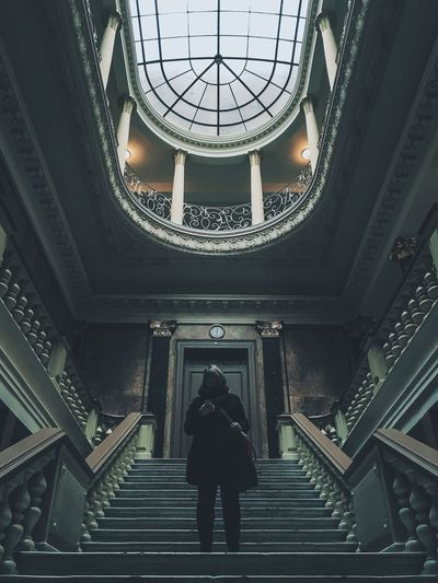 Low angle view of man standing on steps below skylight