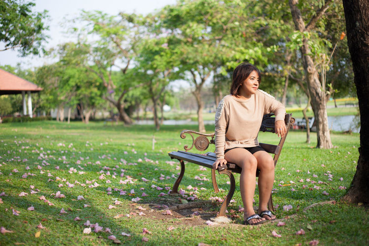 Full Length Of Woman Sitting On Bench At Park