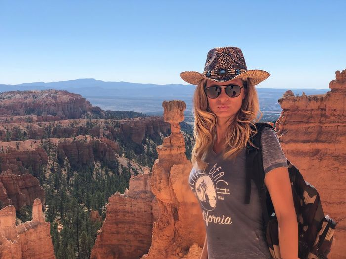 Portrait of woman wearing hat against rocky mountains at bryce canyon