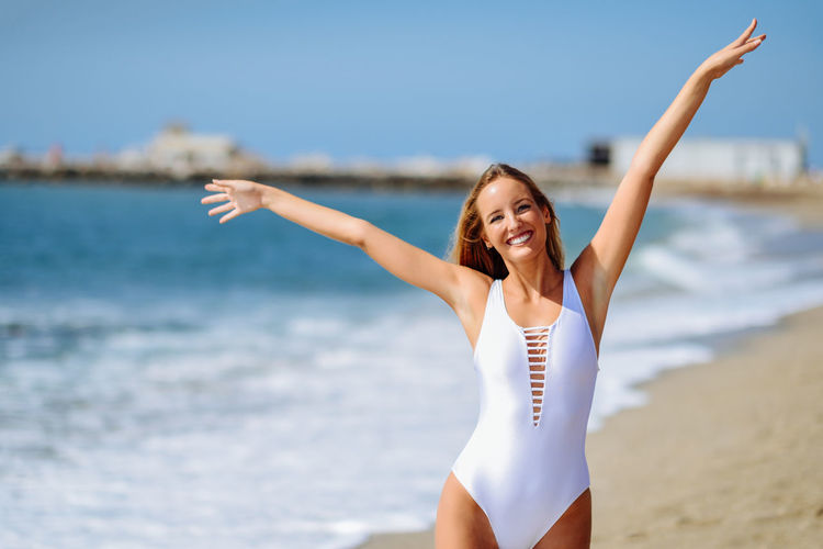 Portrait of cheerful woman with arms raised standing at beach
