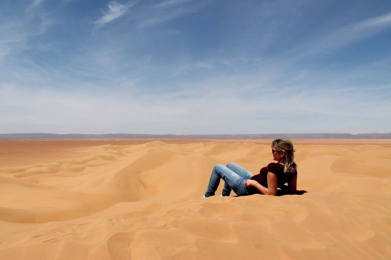Woman Relaxing On Sand At Desert Against Sky