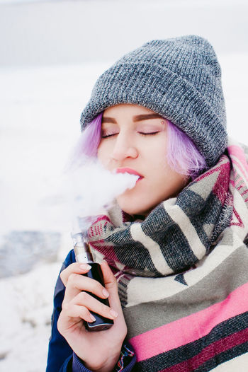 Vaping Addiction Bad Habit Beautiful Woman Close-up Day Focus On Foreground Front View Headshot Holding Human Hand Knit Hat Leisure Activity Lifestyles One Person Outdoors Real People Scarf Smoking - Activity Vape Warm Clothing Winter Young Adult Young Women