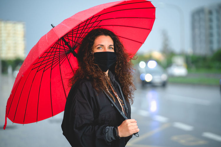Portrait of woman with red umbrella standing in city