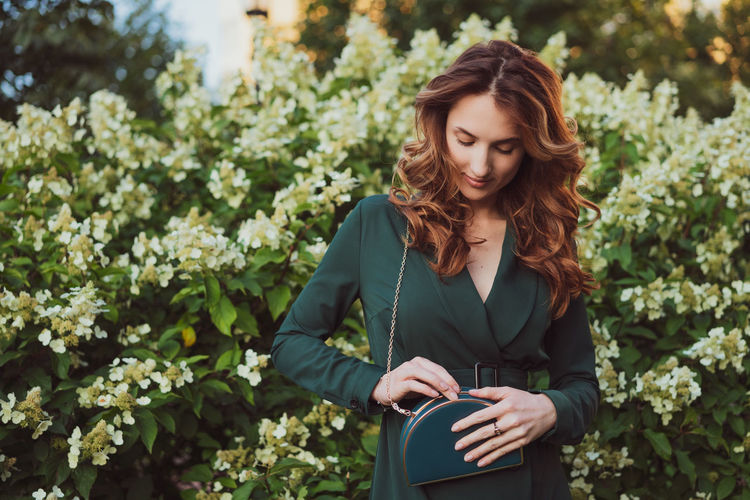 Smiling young woman holding purse while standing against plants