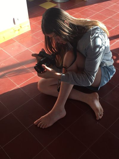 Young woman using mobile phone while sitting on tiled floor