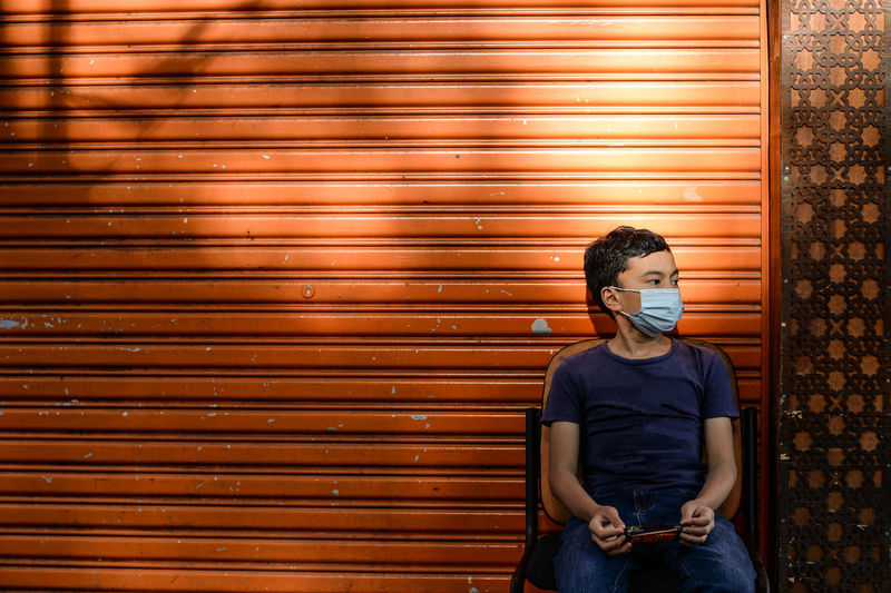 Boy wearing mask looking away while sitting against shutter