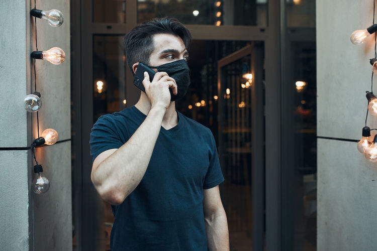 Young man standing in front of restaurant talking on phone using smartphone wearing the face mask