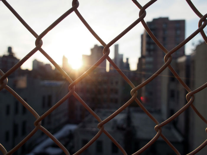 Close-Up Of Chainlink Fence In City During Sunset