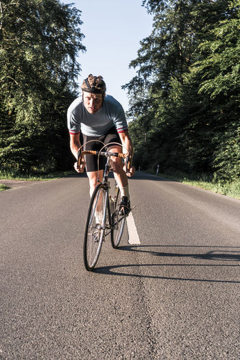 Portrait Of Young Man Riding Bicycle On Road During Sunny Day