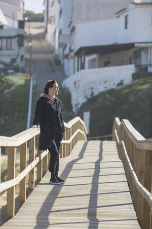 Woman standing on boardwalk. 40-50 Woman Architecture Beach Beautiful Woman Boardwalk Built Structure Casual Clothing Day Focus On Foreground Full Length Leisure Activity Lifestyles Nature One Person Outdoors Railing Real People Shadow Springtime Standing Sunlight Warm Clothing Wooden Young Adult