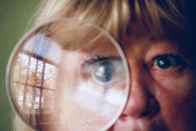 Close-up of woman looking through magnifying glass