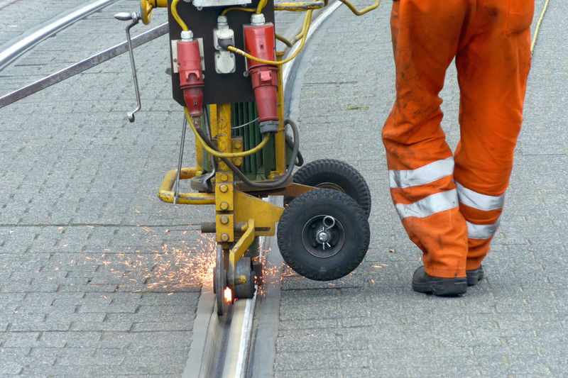 Low section of man with machinery walking on road