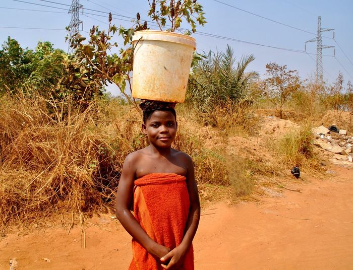 A girl with a water bucket on her head