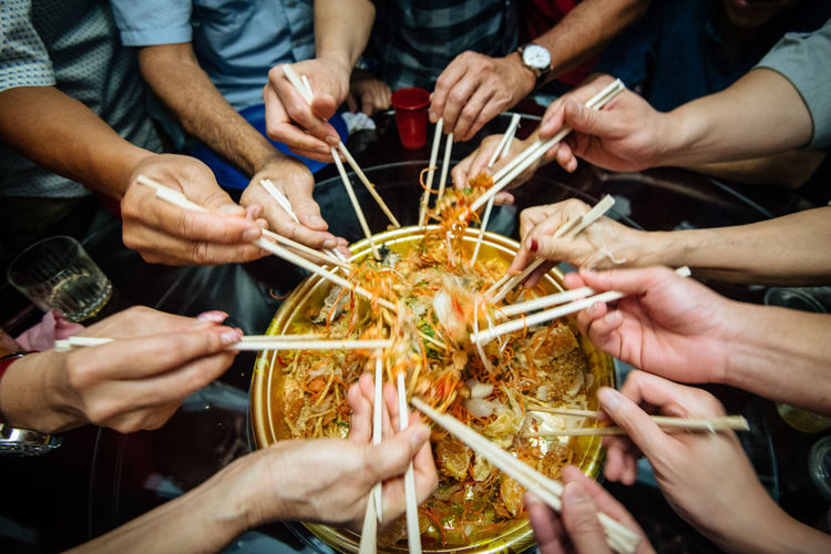 Tradition Adult Celebration Chinese New Year Chopsticks Food And Drink Friendship Group Group Of People Hand Holding Human Hand Indoors  Lifestyles Lohei Medium Group Of People Men Midsection People Real People Shape Teenager Togetherness Women Yusheng A New Perspective On Life