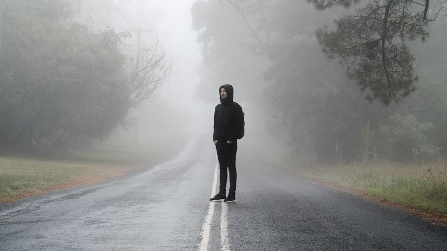 Full length of man standing on country road in forest during foggy weather