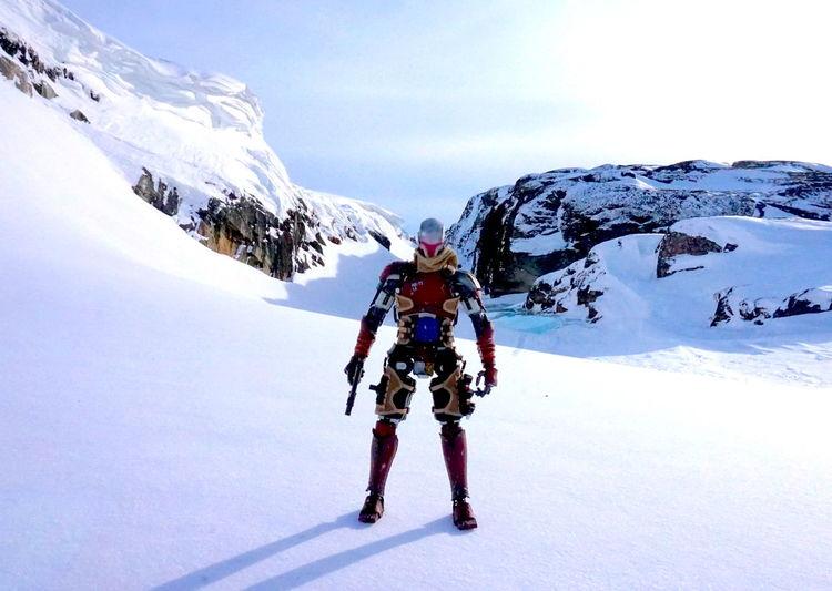 Full length of men on snowcapped mountain against sky