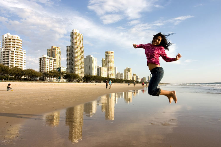 Adult Beach Blue Building Exterior City Cityscape Cloud - Sky Day Full Length Girls Jump Jumping Motion Nature One Girl Only One Person Outdoors People Reflection Sky Skyscraper Travel Destinations Urban Skyline Vacations Water