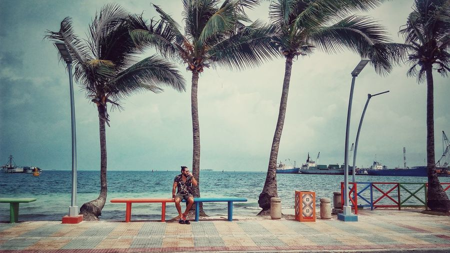 Full length of young man sitting on bench against sky