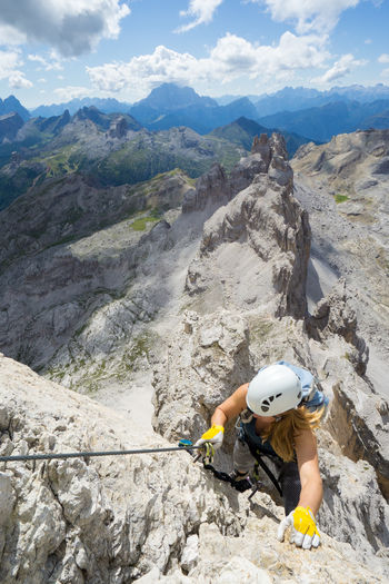 High angle view of woman climbing on rocks against mountains and sky