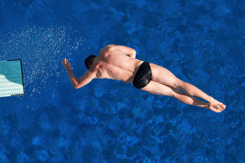 Directly above shot of man jumping in swimming pool