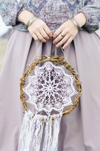 Midsection Of Woman Holding Dreamcatcher