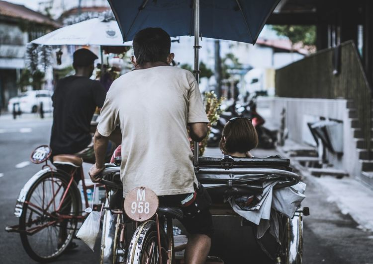 Rear View Of Man Riding Tricycle