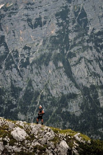 Man Standing On Rock Formation Against Mountain