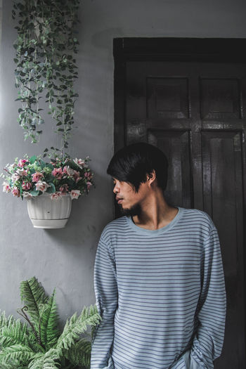 Close-Up Of Young Man Standing By Wall