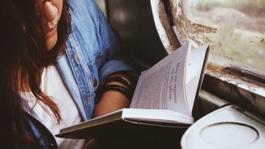 Close-up of young woman reading book