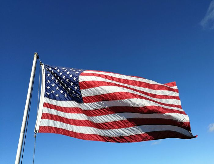 Flag Patriotism Sky Low Angle View Waving US Flag Stars And Stripes Flagpole Red White And Blue
