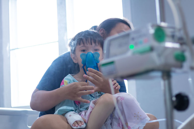 Portrait of cute son wearing oxygen mask with mother in hospital