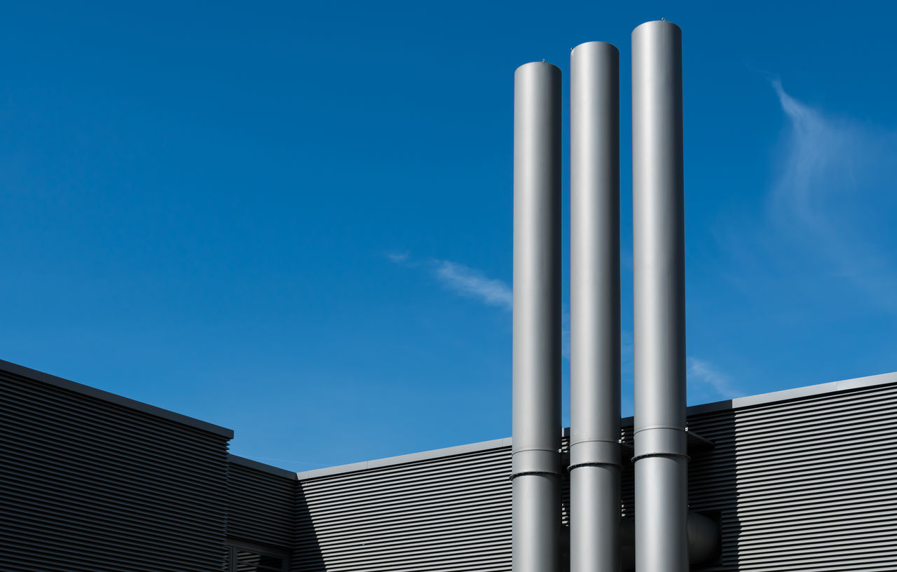 Low angle view of smoke stacks at factory against blue sky