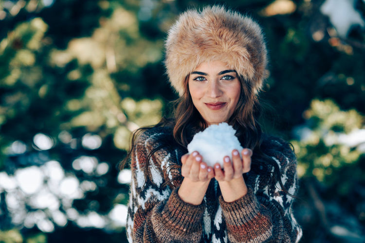 Portrait of beautiful woman standing in park during winter