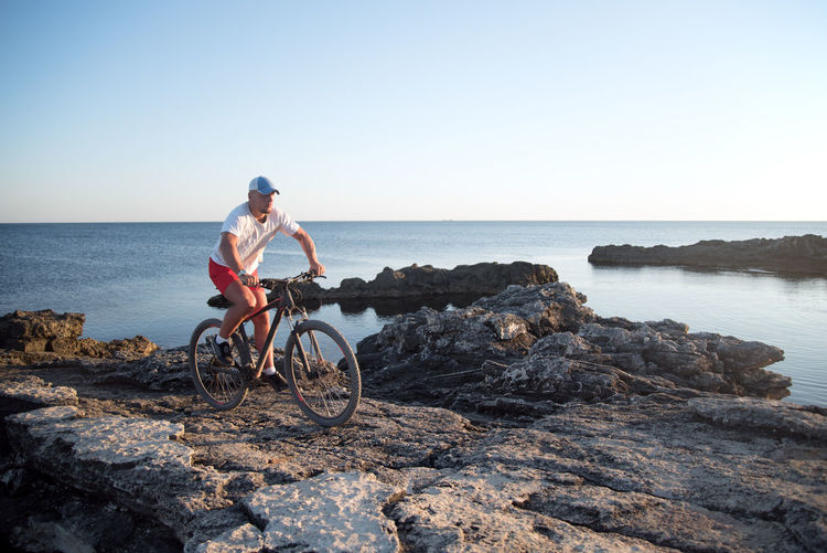 Man riding bicycle on rock by sea against clear sky