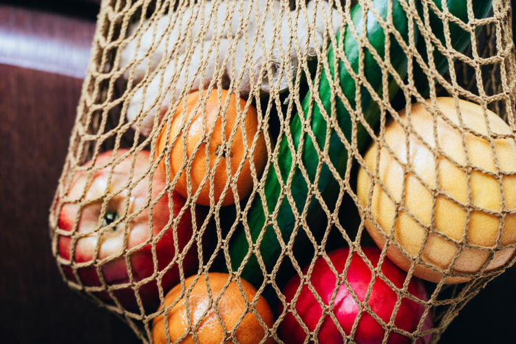 Close-up of vegetables with fruits in mesh bag