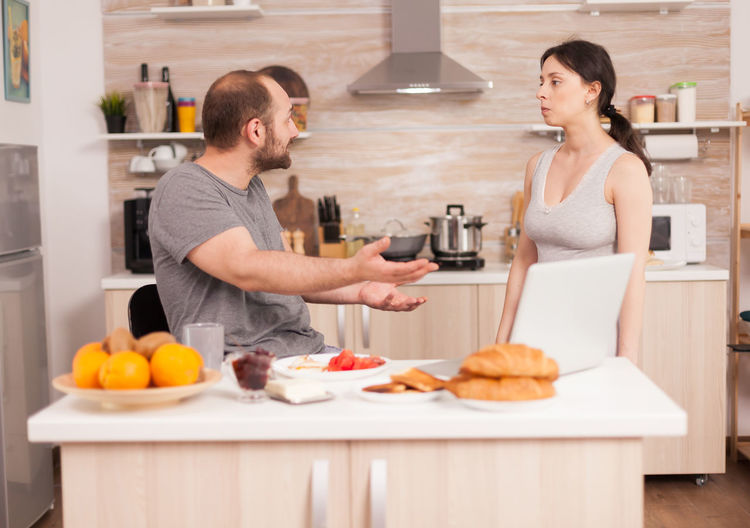 Man and woman standing by food at home