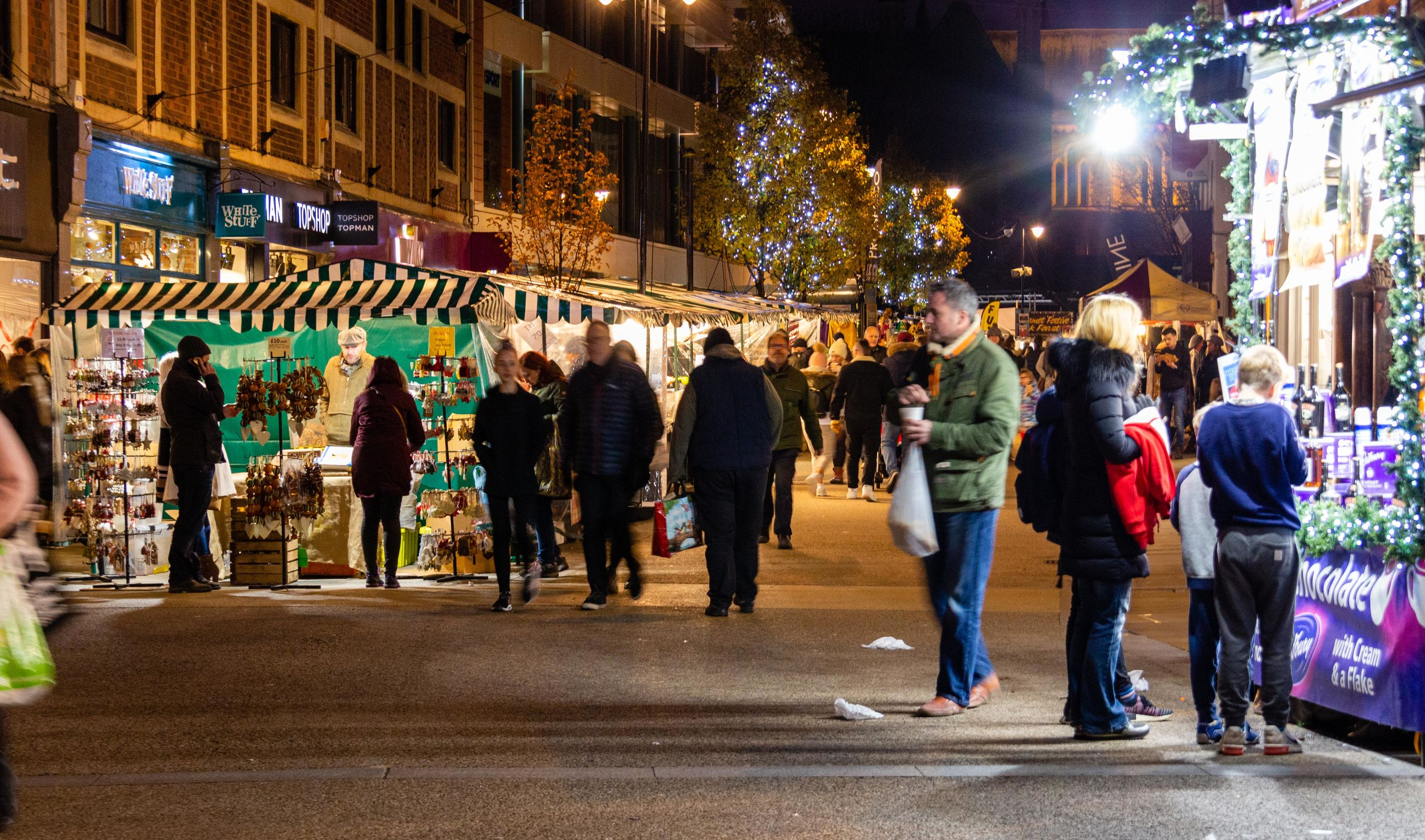 group of people, night, architecture, city, building exterior, illuminated, large group of people, street, crowd, men, real people, women, built structure, adult, city life, lifestyles, walking, motion, lighting equipment, light, street market