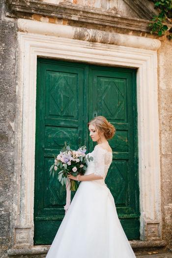 Woman holding bouquet against green door