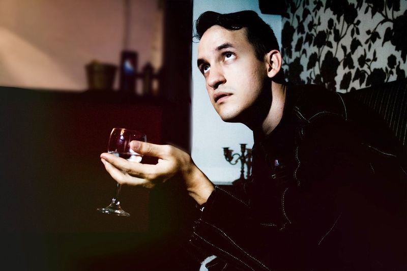 YOUNG Man LOOKING Up Holding Wine Glass